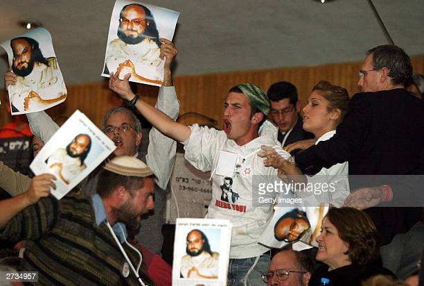 Unidentified protesters raise posters of Jonathan Pollard, an American jailed for spying for Israel in Washington, DC, as they disrupt a speech by...