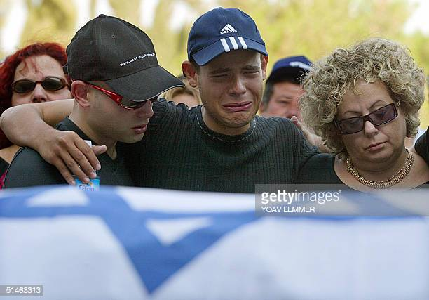 Unidentified relatives of Assaf Greenveld mourn next to his Israeli flagdraped body 11 October 2004 during his funeral at a cemetery in Tel Aviv...