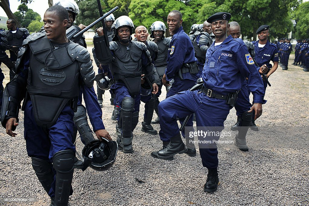 Unidentified riot policemen sing and dance after a demonstration during a graduation ceremony on April 25, 2006 in Kasangulu, outside Kinshasa, Congo, DRC. The European Union has a cooperation and training program with the Congolese police. They trained the integrated Police Unit (UPI) at the Police school here. European standard training and equipment was given to them. These riot police are to be deployed during the upcoming election campaign and elections in Congo, DRC. The country is in ruins after forty years of mismanagement by the corrupt dictator and former president Mobuto Sese Seko. He fled the country in 1997 and a civil war started. The country is planning to hold general elections by July 2006, the first democratic elections in forty years. ,