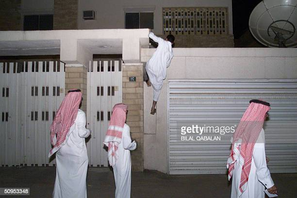 Unidentified Saudi men gather outside the house of a US citizen killed in a driveby shooting 12 June 2004 in Riyadh's Malaz district in the latest in...
