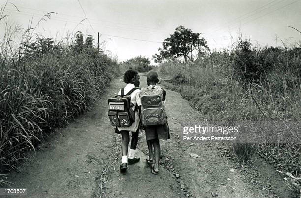 Unidentified schoolgirls walk home from school January 29 2002 in Murhison a rural area outside Port Shepstone in Southern Natal Province in South...