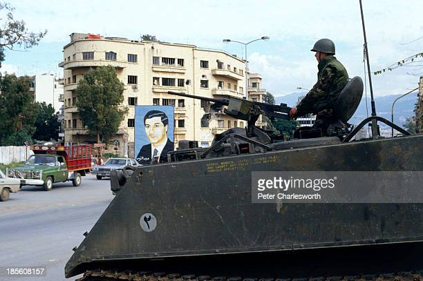 Unidentified solders drive though the streets of war torn Beirut near the 'Green Line' the war zone that divides East and West Beirut and pass by a...