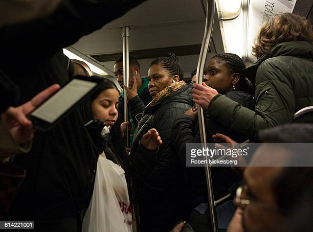 Unidentified subway passengers hold on as the train pulls out of the station during rush hour in New York City on March 14 2016