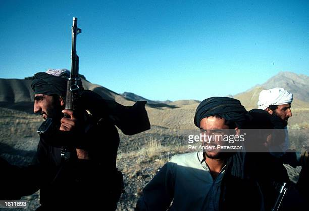 Unidentified Taliban soldiers patrol July 25 1996 outside Kabul Afghanistan The Taliban have taken over most of the country in 1996 and have enforced...