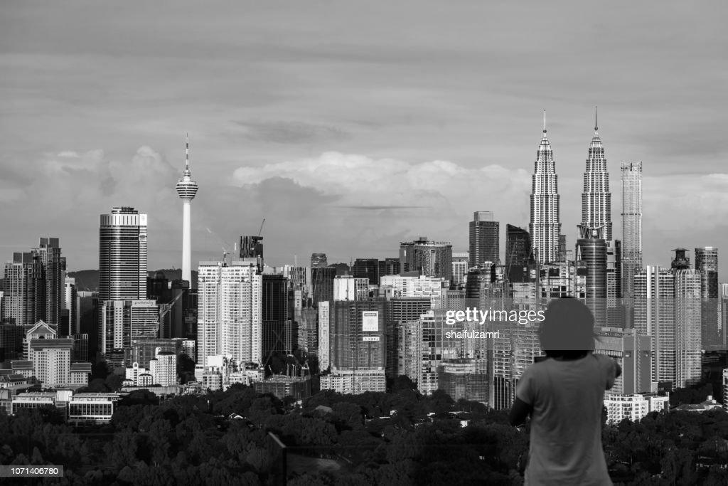 Unidentified tourist shots a picture of morning light over downtown Kuala Lumpur, Malaysia. : Stock Photo