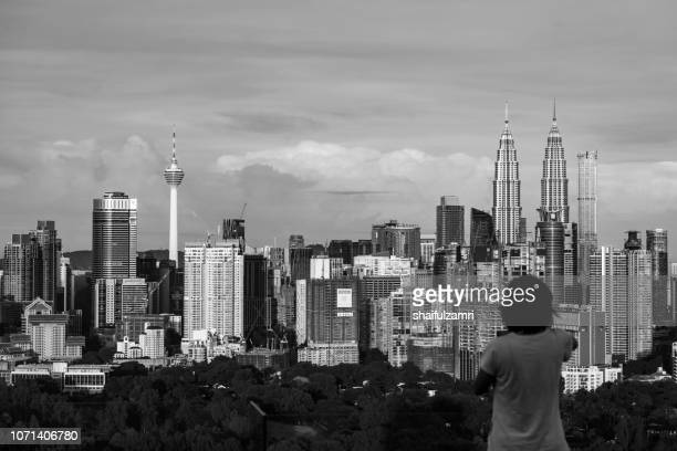 Unidentified tourist shots a picture of morning light over downtown Kuala Lumpur, Malaysia.