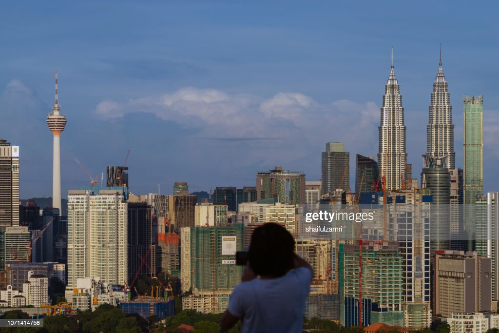 Unidentified tourist shots a picture of morning light over downtown Kuala Lumpur, Malaysia. : Stock Photo