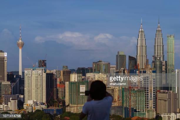 unidentified tourist shots a picture of morning light over downtown kuala lumpur, malaysia. - shaifulzamri 個照片及圖片檔