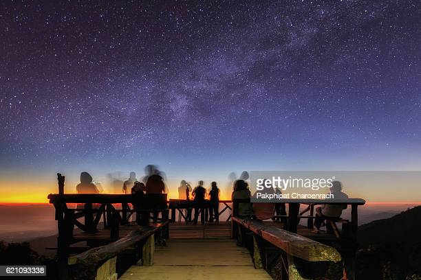 Unidentified tourists are enjoying for milky way at old wooden viewpoint on top of mountain. - (Long exposure / Selective focus)