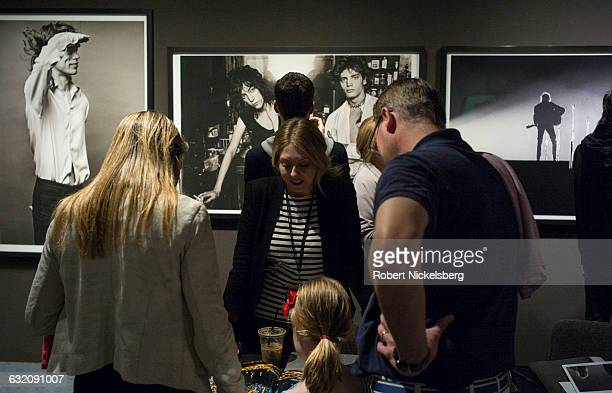 Unidentified viewers gaze at a book of photographs in New York NY on April 17 2016 Many photographs were offered for sale at the annual show held at...