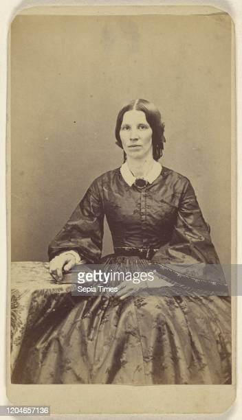 Unidentified woman seated, resting a hand on a book on a table, L.T. Sparhawk , 1870-1879, Albumen silver print.