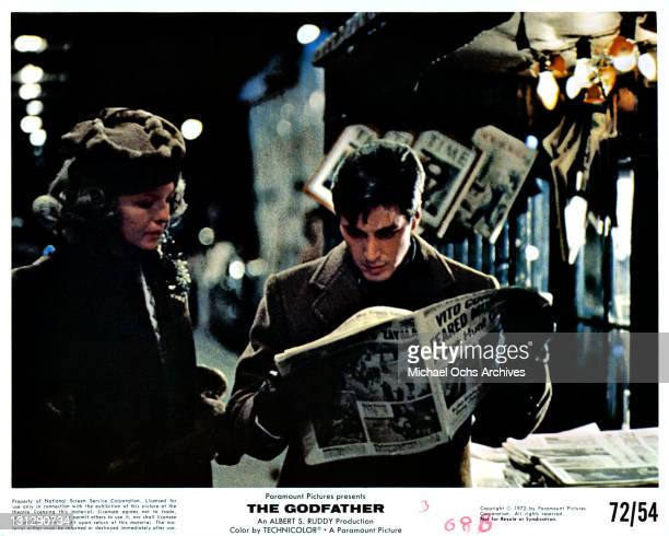Unidentified woman standing next to Al Pacino as he reads the paper in a scene from the film 'The Godfather' 1972