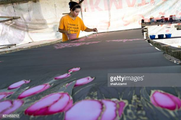 """unidentified woman use dye to make a """"batik"""". making of batik is part of malaysia culture and tourist attraction in kota baharu, kelantan. - shaifulzamri stock pictures, royalty-free photos & images"""