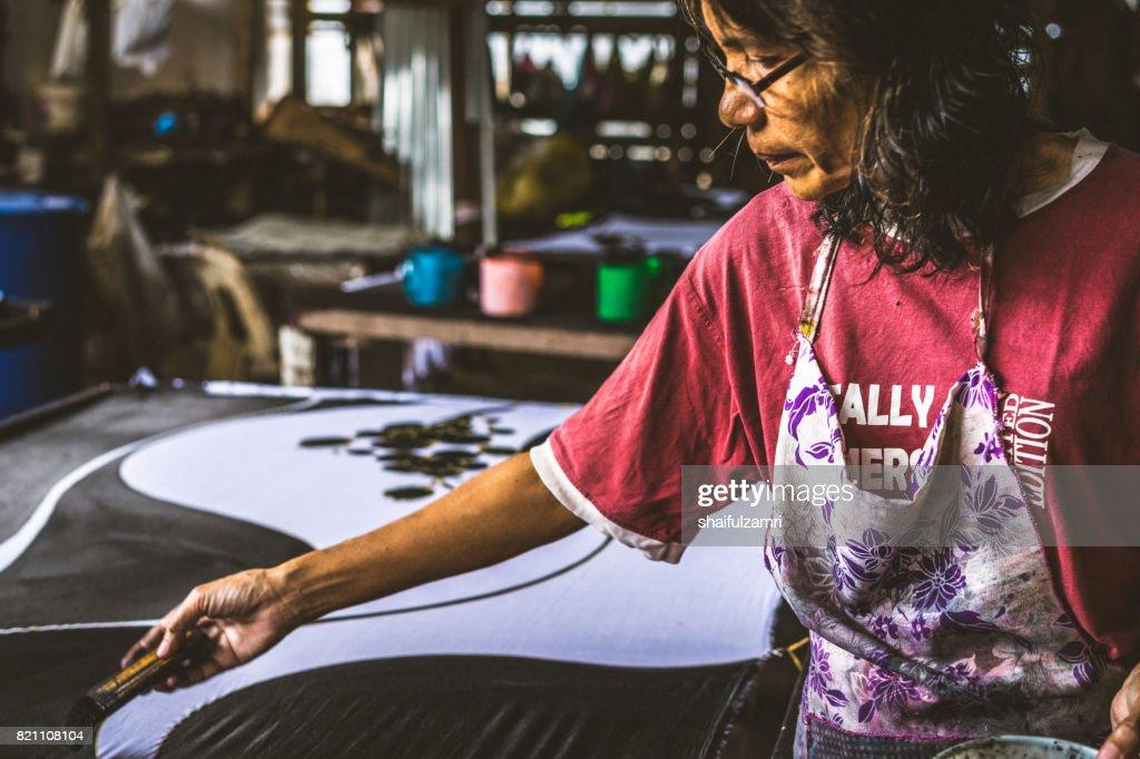 """Unidentified woman use dye to make a """"Batik"""" : Stock Photo"""
