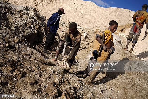 Unidentified young boys carries bags of copper on December 13 2005 in Ruashi mine about 20 kilometers outside Lubumbashi Congo DRC About 4000 young...