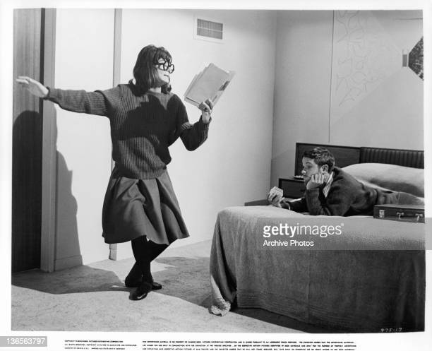 Unidentified young woman performing from book in front of uninterested Michael Anderson Jr in a scene from the film 'Dear Heart', 1964.