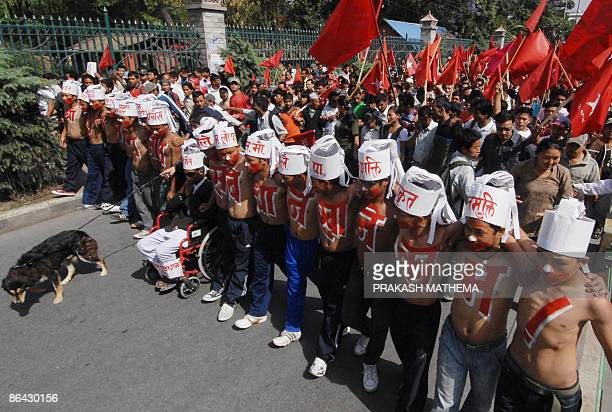 Unified Communist Party of Nepal supporters wear body paint that reads Name His Majesty Ram Baran Job Chew the Constitution in a rally against the...