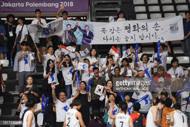 Unified Korea supporters hold up a banner depicting the meeting between North Korean leader Kim Jong Un and South Korean leader Moon Jaein after...