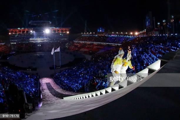 TOPSHOT Unified Korea torchbearers North Korean Jong Su Hyon and South Korean Park Jongah hold the Olympic Flame before the lighting of the cauldron...