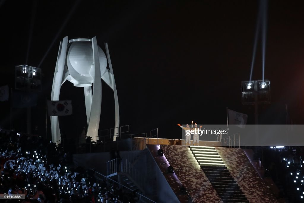 Unified Korea torchbearers, North Korean Jong Su Hyon and South Korean Park Jong-ah hold the Olympic Flame before the lighting of the cauldron during the opening ceremony of the Pyeongchang 2018 Winter Olympic Games at the Pyeongchang Stadium on February 9, 2018. /