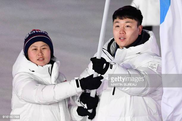 Unified Koreas flagbearer Hwang Chung Gum and Unified Koreas flagbearer Won Yunjong lead the delegation parade during the opening ceremony of the...