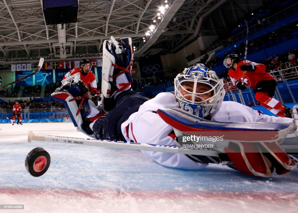 TOPSHOT - Unified Koreas goalkeeper Shin So-jung watches the puck go into the goal shot by Switzerland's Phoebe Staenz (88) during the women's preliminary round ice hockey match between Switzerland and the Unified Korean team during the Pyeongchang 2018 Winter Olympic Games at the Kwandong Hockey Centre in Gangneung on February 10, 2018. / AFP PHOTO / POOL / Brian Snyder