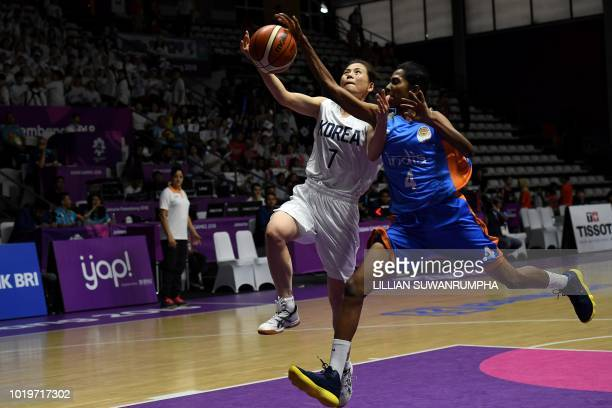 Unified Korea's Jang Mi Gyong goes for the basket against India's Prasannan Geetha Anjana in the women's basketball preliminary match between Unified...
