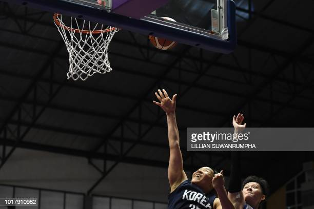 Unified Korea's Kim Hanbyul goes for the basket against Taiwan's Huang Fanshen in the women's basketball preliminary group A match between Taiwan and...