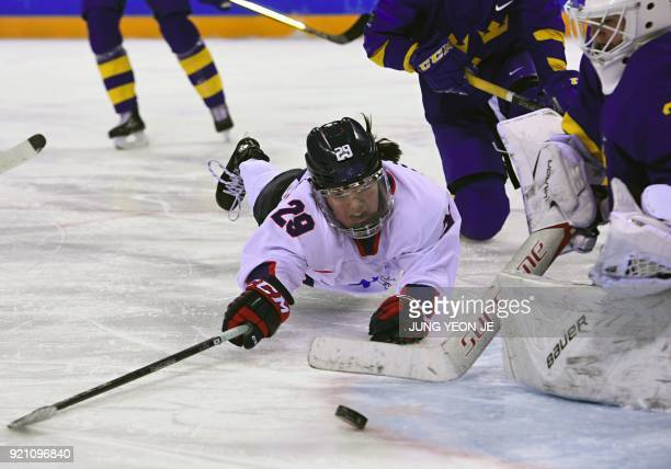 TOPSHOT Unified Korea's Lee Jingyu tries to shoot against Sweden's Sarah Berglind in the women's playoff classifications ice hockey match between the...