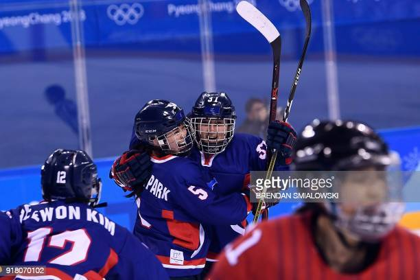 Unified Korea's Randi Griffin cheers with Caroline Nancy Park after scoring in the women's preliminary round ice hockey match between Japan and the...