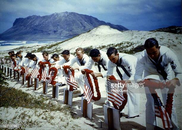 Uniformed American sailors place leis over the graves of the casualities of the attacks on Pearl Harbor the previous December Hawaii spring 1942