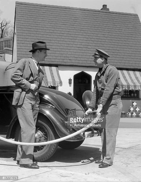 Uniformed Attendant Putting Gasoline In The Tank Of A Coupe While Standing Customer Looks On Smiling 3 Pc.Suit Hat Cap Station Hose Awning.