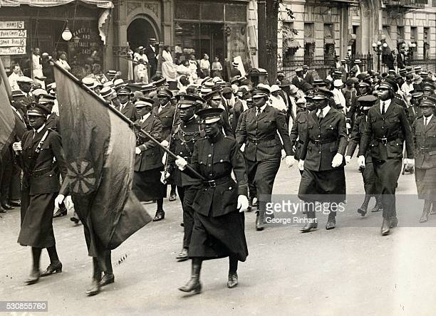 Uniformed attendees to a Marcus Garvey rally carry flags of the movement as they parade up Seventh Avenue in Harlem for a 1924 convention.
