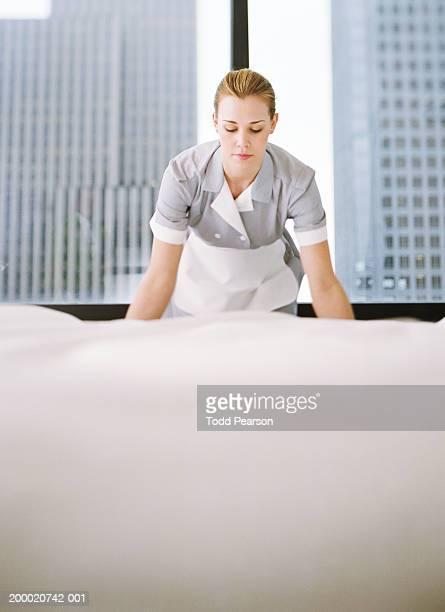 Uniformed hotel maid bent over making bed