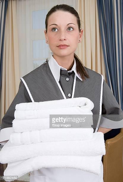 Uniformed criada segurando a pilha de toalhas dobradas