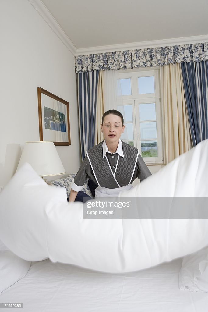Hotel Room Photography: Uniformed Maid Making Bed In Hotel Room High-Res Stock