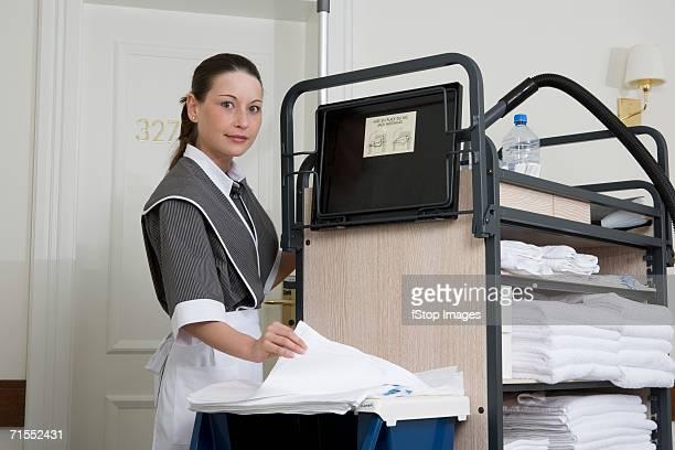 ユニフォームメイドの横にプッシュカートには、ホテルの廊下 - 清掃用具 ストックフォトと画像