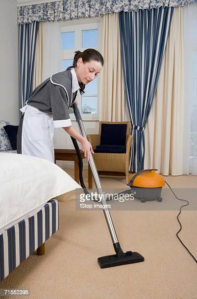 Uniformed maid using vacuum cleaner in hotel room