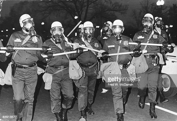 Uniformed members of the Metropolitan Police's Civil Defense Unit in helmets and gas masks patrol the streets during a massive antiVietnam War rally...