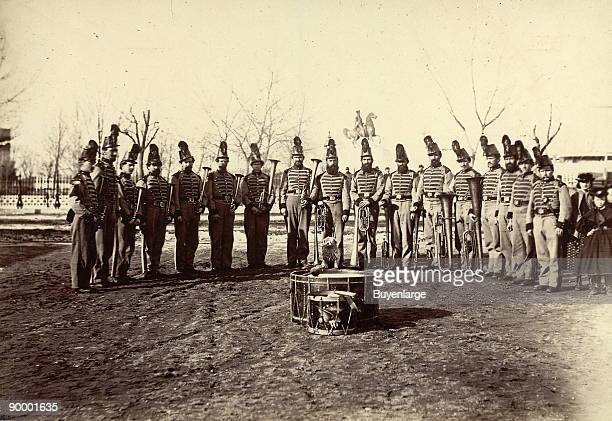 17 uniformed men posed in a semicircle and holding instruments with two drums in foreground