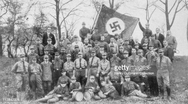 Uniformed officers of Gruppe Spandau SA stormtroopers as they pose for a group portrait beneath a swastika flag in Spandau a borough of Berlin...