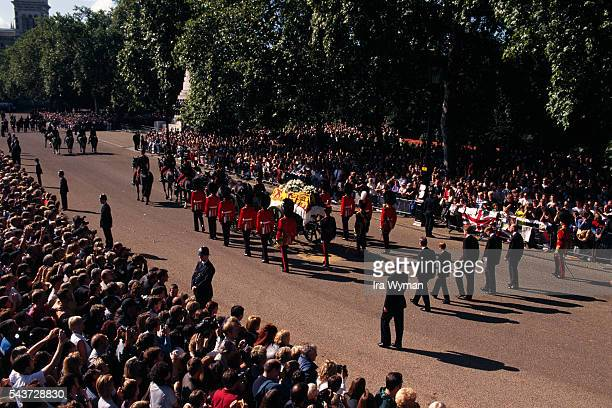 Uniformed pallbearers carry the coffin of Lady Diana Spencer Princess of Wales at her funeral Following behind are Prince Charles and their sons...