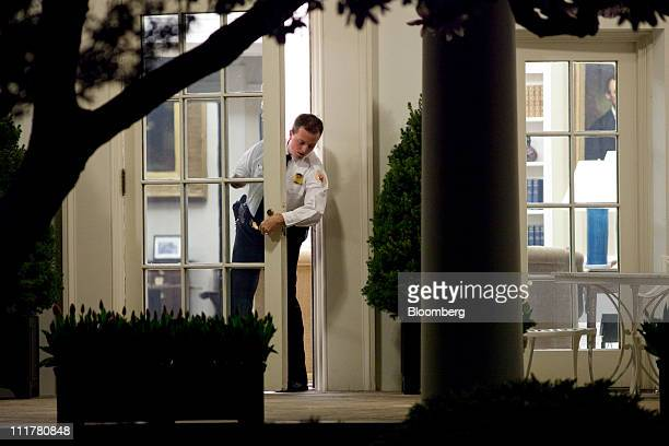 A uniformed secret service officer checks the door of the Oval Office before US President Barack Obama returns to the White House in Washington DC US...