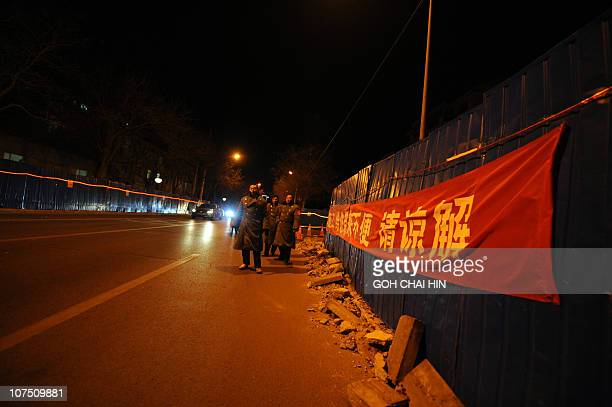 Uniformed security personnel block the road leading to the gate of the apartment complex where jailed Nobel peace laureate Liu Xiaobo's wife lives in...