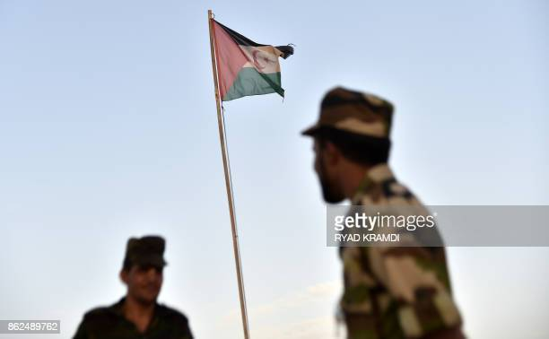 Uniformed soldiers of the proindependence Polisario Front stand before a Sahrawi flag flying at the Boujdour refugee camp near the town of Tindouf in...