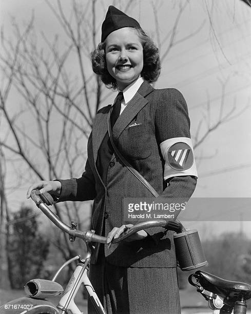 uniformed woman standing and holding bicycle - {{ contactusnotification.cta }} stockfoto's en -beelden