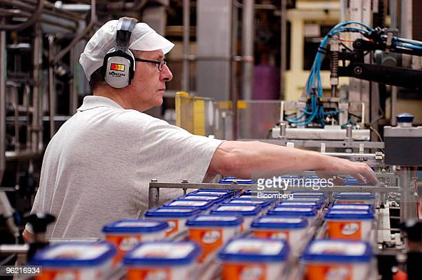 Unilever employee inspects Becel margarine tubs as they move along a conveyor belt at the Unilever factory in Rotterdam The Netherlands September 16...
