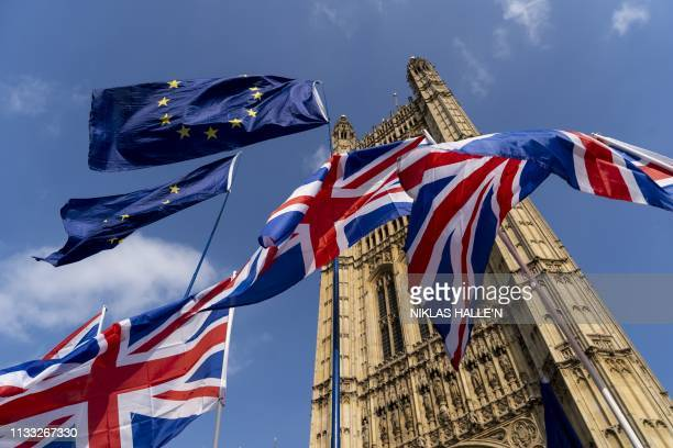 Union and EU fags flutter outside the Houses of Parliament in Westminster, London on March 28, 2019. - Faced with losing all control over the Brexit...