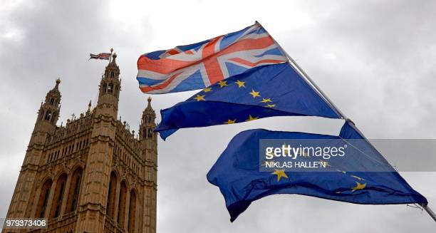 Union and European Union flags are flown in unison during an antiBrexit demonstration outside the Houses of Parliament in London on June 20 2018...
