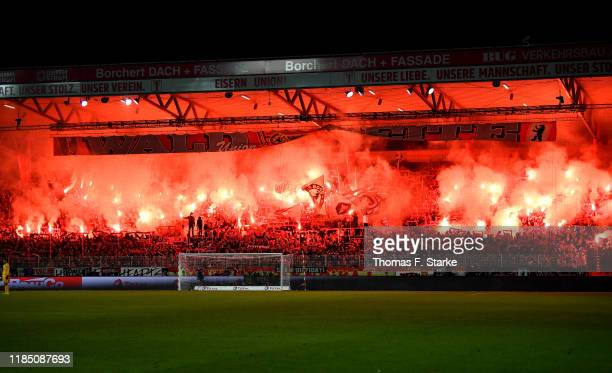 Union Berlin let off flares as they show their support during the Bundesliga match between 1. FC Union Berlin and Hertha BSC at Stadion An der Alten...